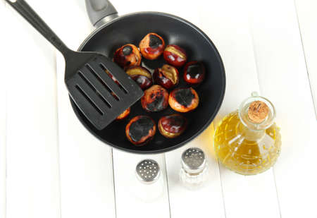 buckeye seed: roasted chestnuts in the pan and decanter with oil, salt and pepper on white wooden background