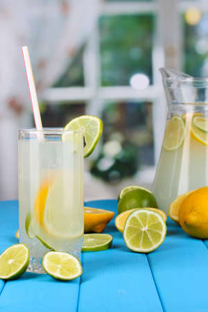 Citrus lemonade in pitcher and glass of citrus around on blue wooden table on window background Stock Photo - 15765189