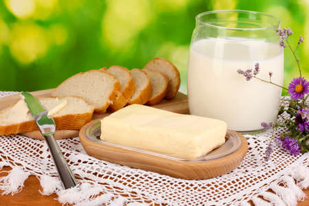 Butter on wooden holder surrounded by bread and milk on natural background Stock Photo - 15765306