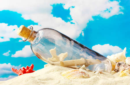 Glass bottle with note inside on sand, on blue sky background photo
