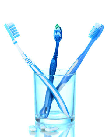 Toothbrush in glass and chewing gum on blue background photo