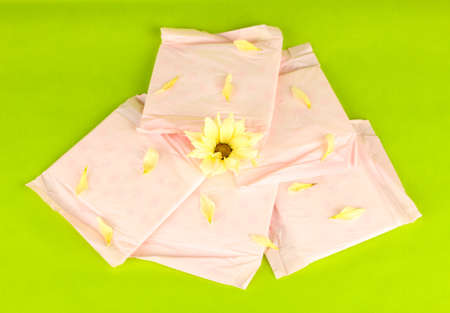 Panty liners in individual packing and yellow flower on green background close-up photo