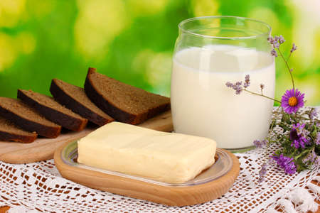 Butter on wooden holder surrounded by bread and milk on natural background Stock Photo - 15773628