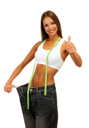 lose weight: beautiful young woman with big jeans and measuring tape, isolated on white Stock Photo