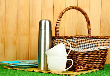 airtight: metal thermos with cups, plates and basket on grass on wooden background