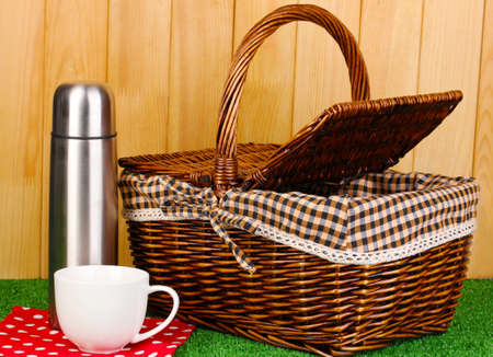 airtight: metal thermos with cup and basket on grass on wooden background