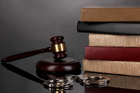magistrate: Gavel, handcuffs and books on law isolated on black Stock Photo