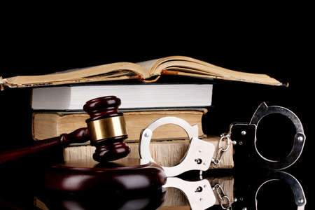 adjournment: Gavel, handcuffs and books on law isolated on black close-up