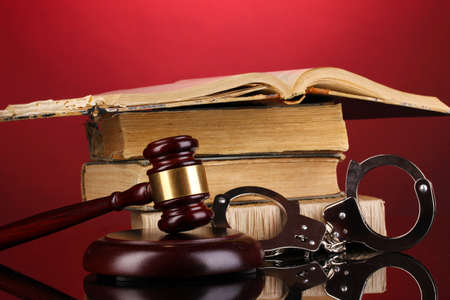 magistrate: Gavel, handcuffs and book on law on red background