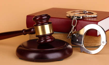 Gavel, handcuffs and book on law on beige background