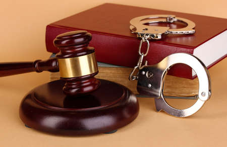 judicial proceeding: Gavel, handcuffs and book on law on beige background