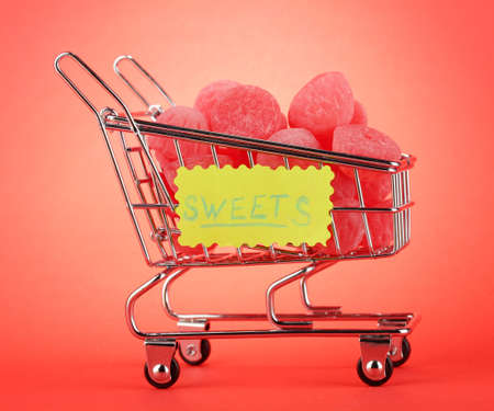 shopping trolley with jelly candies, on red background Stock Photo - 15772962