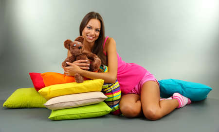 beautiful young girl and fluffy bear with pillows on grey background photo