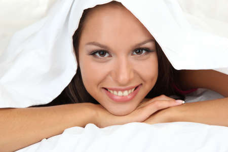 coverlet: young beautiful woman looking out from coverlet Stock Photo