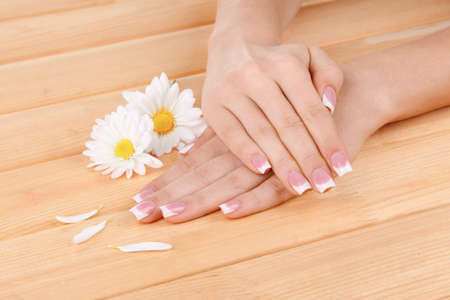 Woman hands with french manicure and flowers on wooden background photo
