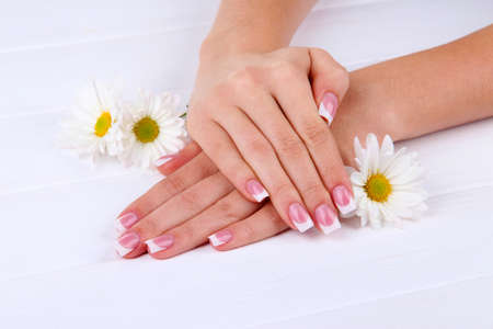 manicure salon: Woman hands with french manicure and flowers on white wooden background