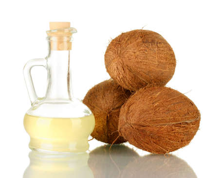 decanter with coconut oil and coconuts isolated on white photo