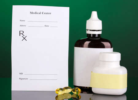 Pharmacist prescription with drops and pills isolated on green photo