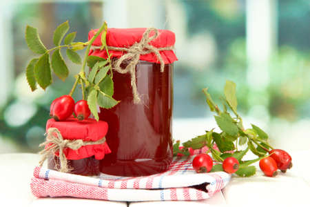 canned fruit: jars with hip roses jam and ripe berries, on wooden table Stock Photo