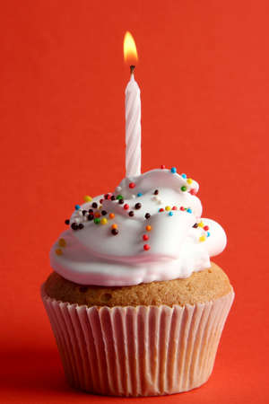 tasty birthday cupcake with candle, on red background photo