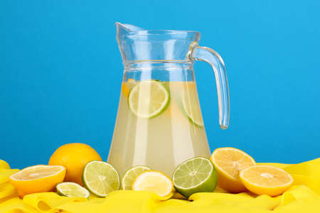 Citrus lemonade in glass pitcher of citrus around on yellow fabric on blue background Stock Photo - 15831174