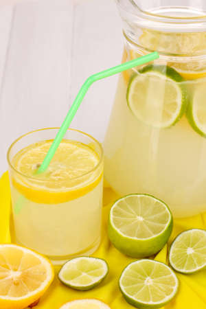 Citrus lemonade in glass and pitcher of citrus around on yellow fabric on white wooden table close-up Stock Photo - 15830828