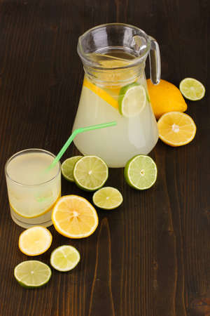 Citrus lemonade in glass and pitcher of citrus around on wooden table close-up Stock Photo - 15831239