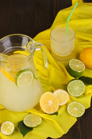 Citrus lemonade in glass and pitcher of citrus around on yellow fabric on wooden table close-up Stock Photo - 15847365