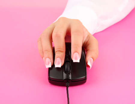woman's hands pushing keys of pc mouse, on pink background close-up photo