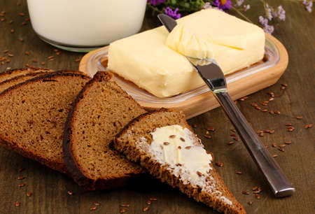 Butter on wooden holder surrounded by bread and milk on wooden table close-up photo