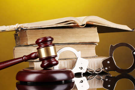 Gavel, handcuffs and book on law on yellow background Stock Photo - 15831193