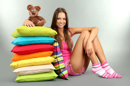 beautiful young girl and fluffy bear with pillows on grey background Stock Photo - 15960405