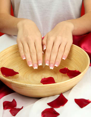 woman hands with wooden bowl of water with petals, on red background Stock Photo