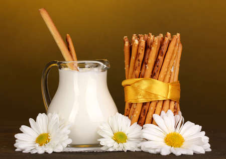 Tasty crispy sticks with pitcher with sour cream on wooden table on yellow background photo