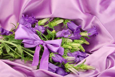 purple silk: azules flores de campana en la tela de seda p�rpura Foto de archivo