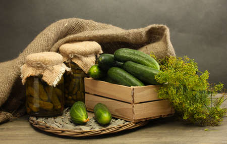 fresh cucumbers in wooden box, pickles and dill, on grey background photo