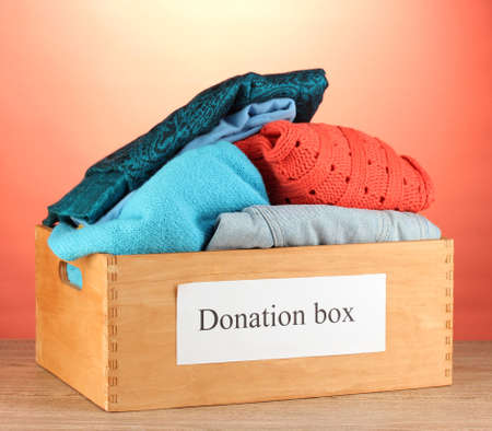 warm clothes: Donation box with clothing on red background close-up Stock Photo