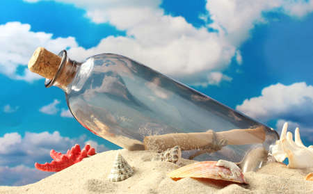 Glass bottle with note inside on sand, on blue sky background Stock Photo - 15852177