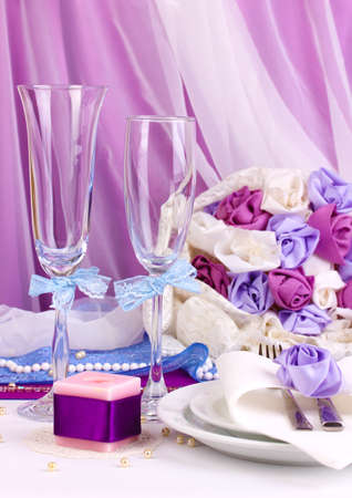 wedding table decor: Serving fabulous wedding table in purple color on white and purple fabric background Stock Photo