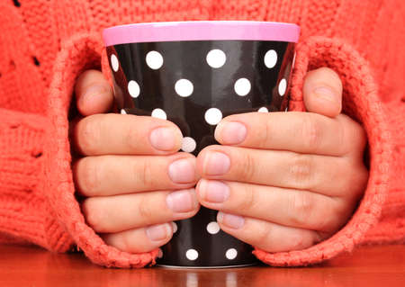 hands holding mug of hot drink close-up photo