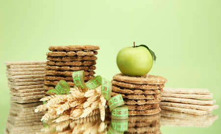 tasty crispbread, apple, measuring tape and ears, on green background photo