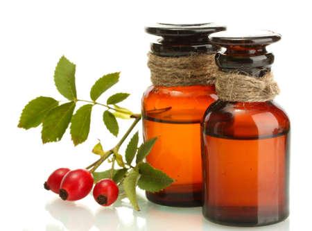 medicina natural: frascos de medicinas con rosas cadera, aislado en blanco