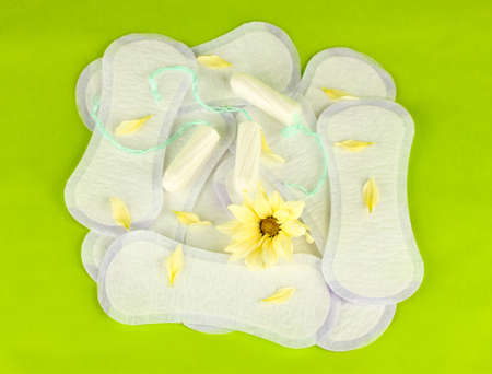 sanitary pads and tampons on green background close-up Stock Photo - 15852062