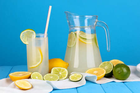 Citrus lemonade in pitcher and glass of citrus around on wooden table on blue background Stock Photo - 15852204