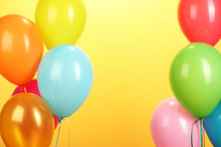 colorful balloons on yellow background close-up