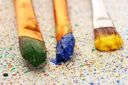 brushes with colorful paint on colorful splashes background close-up Stock Photo