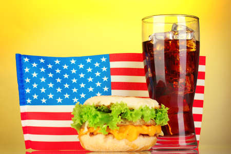 tasty sandwich and cola with american flag, on yellow background photo