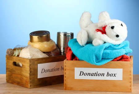 Donation boxes with clothing and food on blue background close-up Stock Photo - 15898078