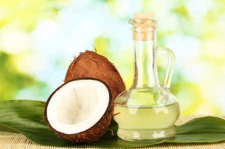 aceite de coco: jarra con aceite de coco y el coco sobre fondo verde