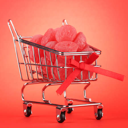 shopping trolley with jelly candies, on red background photo